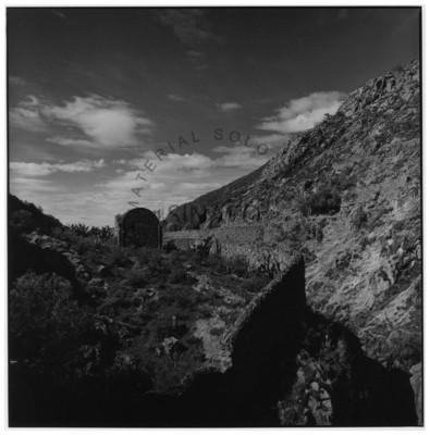 Construcción y muro de piedra junto a cerro