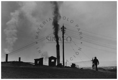 Minero camina frente a instalación eléctrica y chacuaco