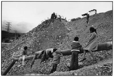 Niños observan a mineros durante descarga de mineral