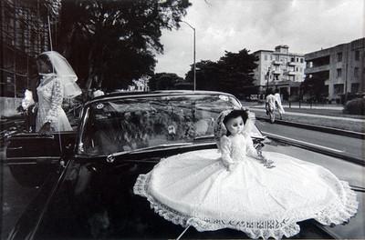 Mujer vestida de novia y muñeca sobre el cofre de automóvil