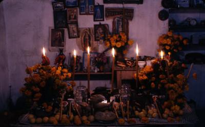 """Altar"" de ""Chalcatzingo"" con flores, velas e imágenes religiosas"