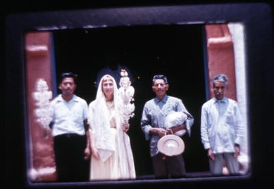 Mujer y hombre sujetan velas adornadas con papel en la entrada de la iglesia de Amatlán