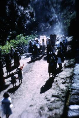 Hombres, mujeres y niños caminan rumbo a iglesia en procesión