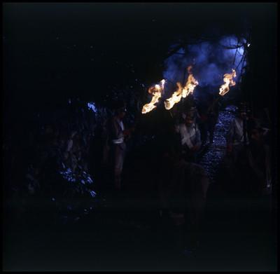 Soldados transitan por un camino alumbrándose con antorchas, escena del Señor de Osanto