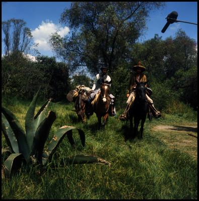 Farnesio de Bernal y otro actor montan a caballo mientras caminan por una pradera