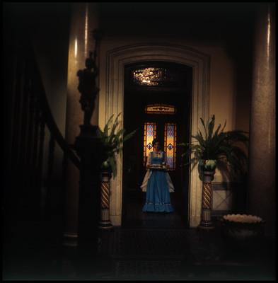Actriz camina por el pasillo de la casa mientras sostiene una charola con tazas