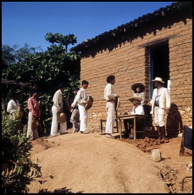 Escena de indígenas afuera de vivienda