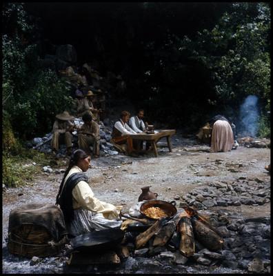 Escena de hombres comiendo en el campo con gente indígena
