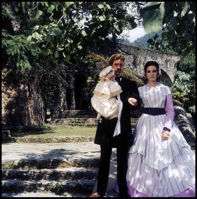 Hugo Stiglitz carga a una niña mientras pasea con una actriz por un jardin, escena de la película El Señor de Osanto