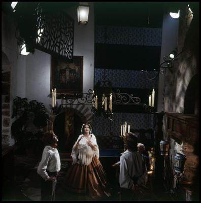 Actores miran hacia arriba, en el interior de una casa. Escena