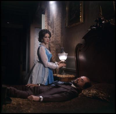 Actriz enciende lampára y observa a Farnesio de Bernal acostado sobre una cama