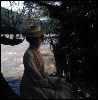 Mujer sentada a la orilla de río