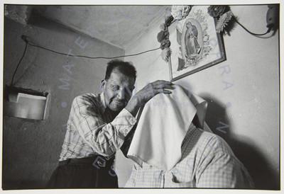 Hombre ciego toca la cabeza curbierta de otro hombre, interior de habitación