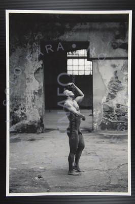 Hombre de pie posa desnudo y mira hacia arriba, retrato de perfil