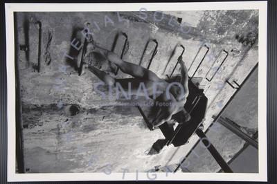 Hombre desnudo de espaldas sobre una escalera de metal, retrato