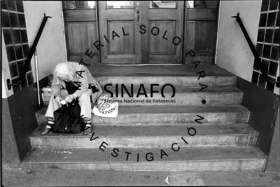 Mujer sentada en escalones a la entrada de un edificio