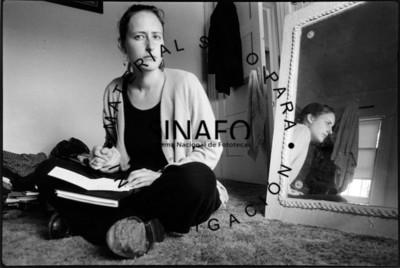 Mujer sentada se refleja en espejo, interior de habitación
