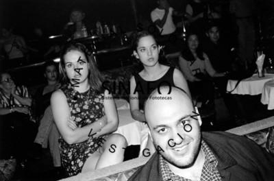 Hombre sonríe, detrás de él dos mujeres sentadas con los brazos cruzados, retrato