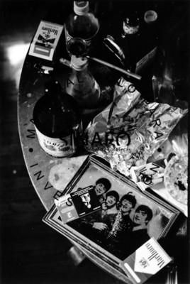 Mesa con cajetillas de cigarros, refresco y objetos diversos