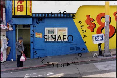 Hombre de pie en una calle, porta saco y sombrero, lleva bolsas de plástico, retrato