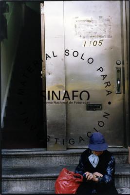 Mujer con sombrero sentada en escalones a la entrada de edificio, retrato