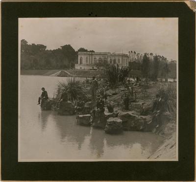 Hombres sentados junto al lago mayor y al fondo el Club del automóvil