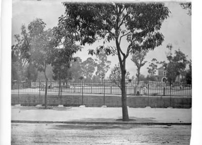 Reja de hierro que limita el terreno para ubicar las jaulas de las fieras y al fondo la iglesia que fue demolida