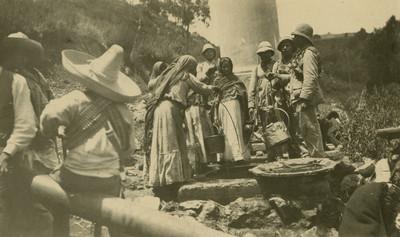 Mujeres y militares obtienen agua de un pozo