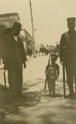 Niño con uniforme de militar y rifle junto a hombres, retrato