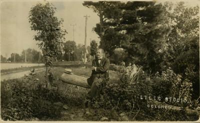 Hombre sentado en un tronco, tarjeta postal