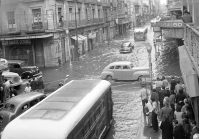 Gente observa transitar automóviles en la esquina 16 de septiembre con Isabel la Católica inundada