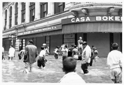 Gente frente al edificio Boker camina por la calle inundada