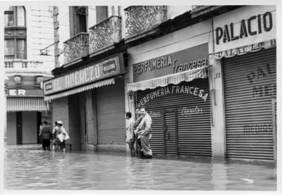 Hombres sobre la avenida 16 de septiembre inundada