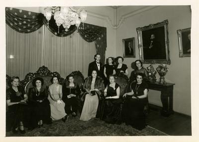 Mujeres y hombre en una sala, retrato de grupo