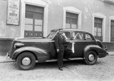 Hombre junto a un automóvil estacionado