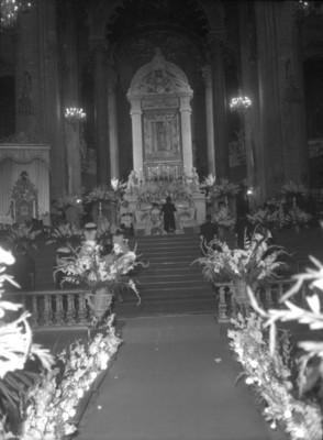 Novios hincados durante su boda religiosa, vista posterior