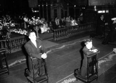 Hombres y mujer hincados durante una boda religiosa