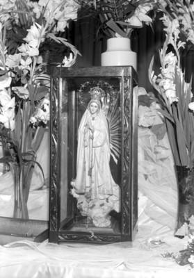 Virgen en un nicho rodeada de flores