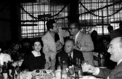 José Vasconcelos sentado a la mesa, mientras varias personas conviven, durante un banquete en un salón