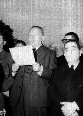 José Vasconcelos acompañado por varias personas, dando lectura a un discurso, durante una ceremonia