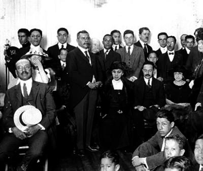 José Vasconcelos acompañado por varias personas, probablemente durante una ceremonia en un salón