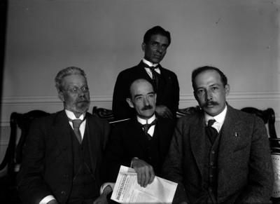 Carlos B. Zetina acompañado de tres hombres en una sala, retrato de grupo