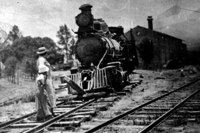 Hombre y niño en una estación del ferrocarril, observando una locomotora