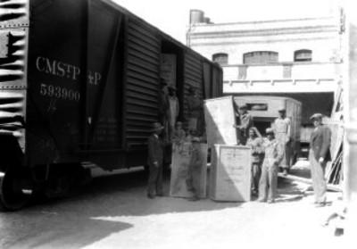 Estibadores con cajas de majestic, junto a un furgón en el área de servicio de carga de una estación ferroviaria