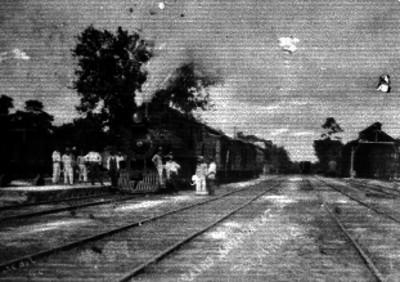 Hombres parados junto a un ferrocarril en una estación entre Tapachula y Suchiate Chiapas