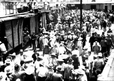 Gente abordando un vagón de carga en la estación Colonia