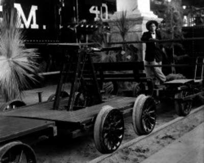 Hombre junto a un armón en los patios de una estación del ferrocarril, retrato