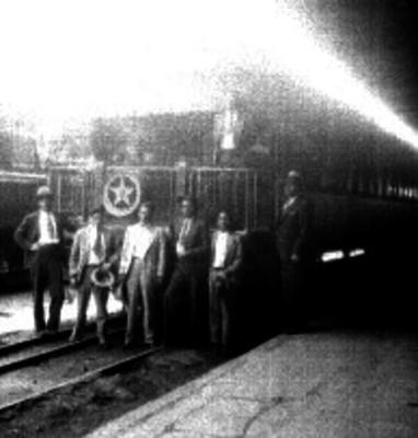 Hombres vestidos de traje junto al cabú de un tren de pasajeros, en una estación ferroviaria, retrato de grupo