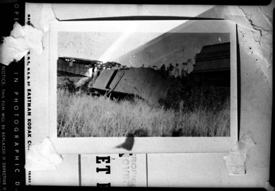 Ferrocarrileros sobre la vía junto a una locomotora accidentada