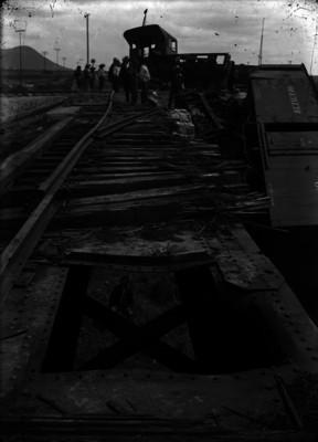 Ferrocarrileros viendo un ferrocarril descarrilado a las orillas de una vía